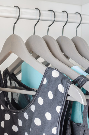 row of dress hanging on coat hanger in wardrobe photo
