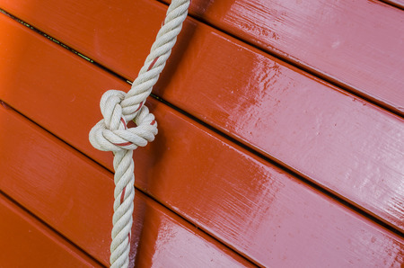 fixed line: Rope knot and wood panel background Stock Photo