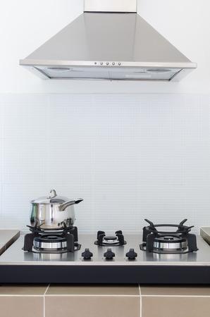 estufa: inoxidable sart�n sobre la estufa de gas con la capilla de cocina