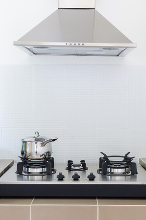 stainless pan on gas stove with hood in kitchen