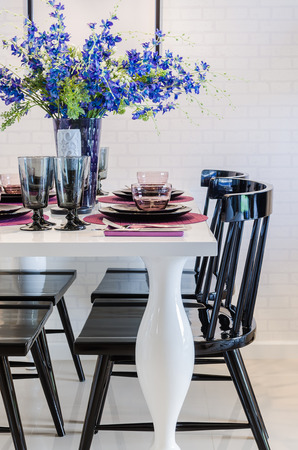 dinning table: flower on white dinning table with black chair in dinning room Stock Photo