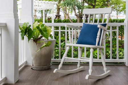 bílým dřevěné houpací křeslo na verandě