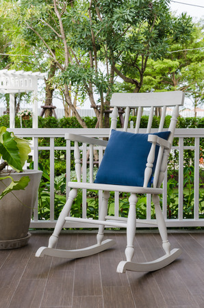 white wooden rocking chair on front porch at home photo