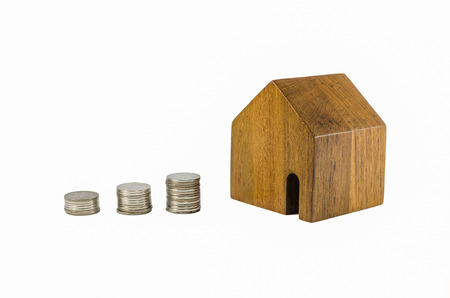 dearness: wooden toy house with coins concept of dearness of habitation on white background