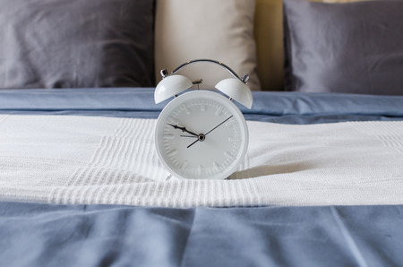 modern white alarm clock design on bed photo