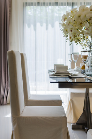 table set in white dinning room at home photo