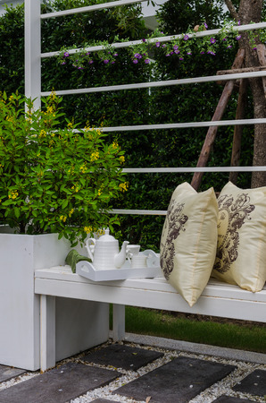 tea set: tea set and yellow pillows on white bench in garden Stock Photo