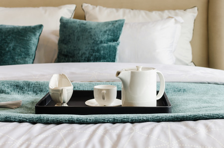hotel suite: tea set on black tray in modern bedroom at home