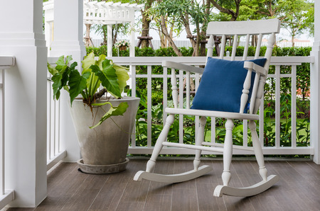 deck chairs: white wooden rocking chair on front porch