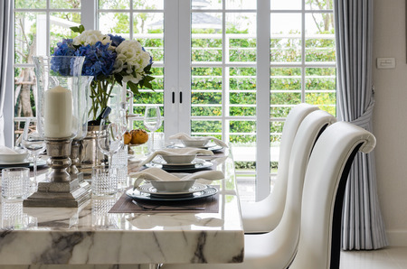 table set in white dinning room with chairs at home photo