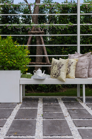 tea set and yellow pillows on white wodden bench in garden