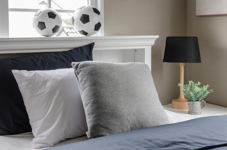 white bed with pillow and  football on top at home photo