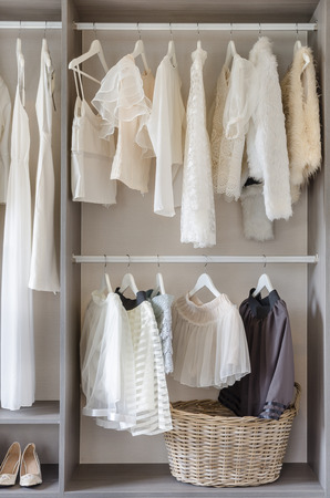 row of white dress with shoes in wardrobe at home