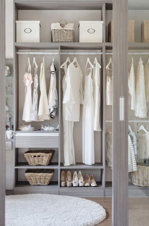 row of white dress with shoes in wardrobe at home photo