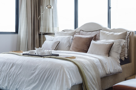 tea cup set on classic bed with pillows at home