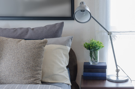 bedroom suite: modern lamp on wooden table in bedroom at home Stock Photo