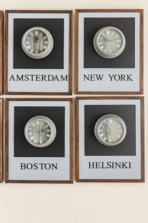 time zones: clock diferent time zones on the wall