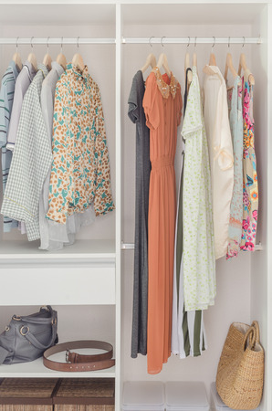 clothing rack: white closet with dress hanging on coat hanger at home