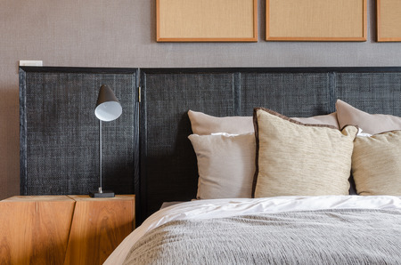 chambre � � coucher: lit moderne noir avec des oreillers et une lampe dans la chambre � la maison Banque d'images