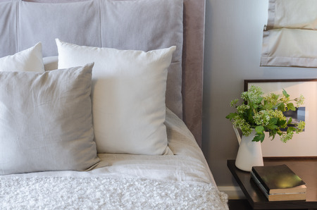 white pillows on white bed with vase of plant on table at home