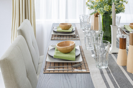 ware house: table set on wooden dinning table with wooden bowl at home Stock Photo