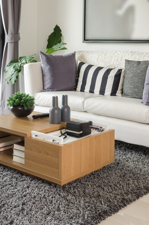 sitting room lounge: white sofa with wooden table in modern living room at home Stock Photo