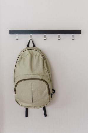 backpack: mochila verde que cuelga en la pared Foto de archivo