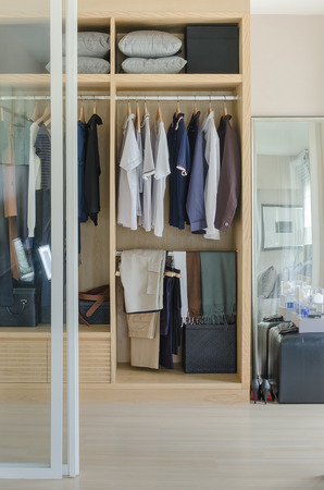 walk in closet: walk in closet with clothes hanging in wooden wardrobe at home