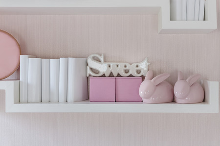 white boxes: Decorative shelf on pink wall with rabbits ceramic and word sweet at home Stock Photo