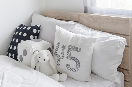 bedroom: black and white pillows with doll on wooden bed in kids bedroom at home Stock Photo