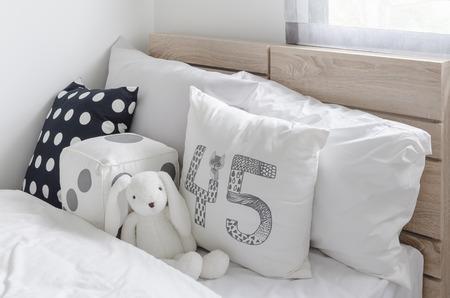 chambre � coucher: oreillers en noir et blanc avec la poup�e sur le lit en bois dans la chambre des enfants � la maison