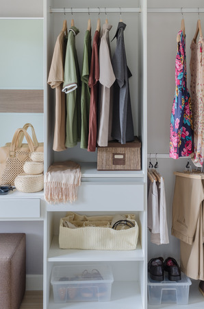 white closet with clothes, shirts, and accesories at home