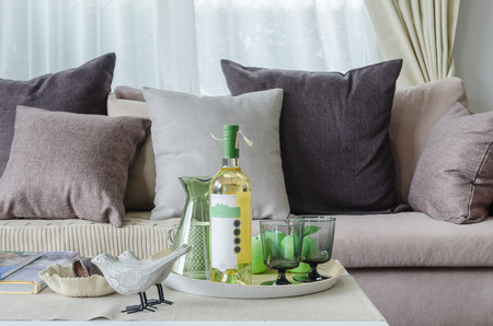 curtain design: pillows and blanket on earth tone sofa with set of wine in living room at home