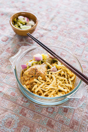 soi: Thai northern curry noodle with chicken in glass bowl (Khao Soi)