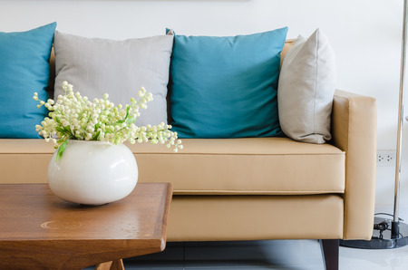 sofa: plant in ceramic vase on wooden table with modern sofa at home Stock Photo