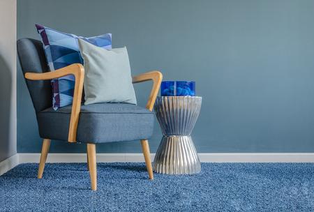 リビング ルームのカーペットの上に青い色枕と木製の椅子