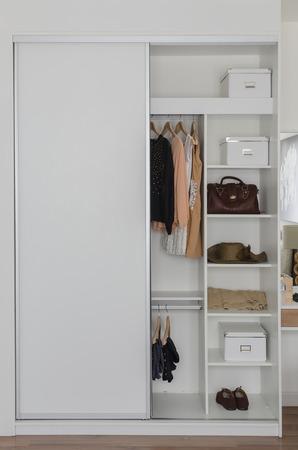 ropa colgada: armario blanco con ropa y complementos en el hogar