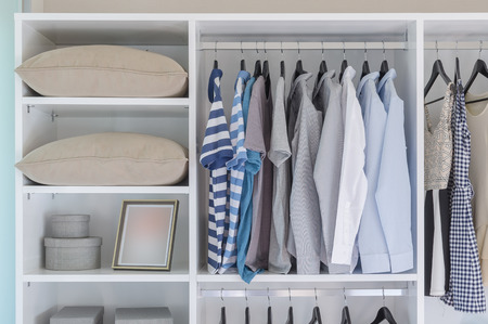 clothes hanging in white wardrobe with pillows and boxes Stockfoto