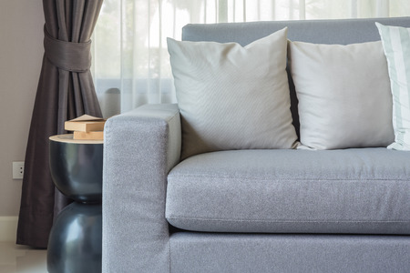 sofa: modern grey sofa with pillows in living room at home Stock Photo
