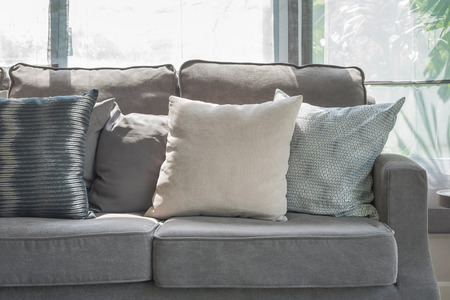 modern living: pillows on modern grey sofa in living room at home