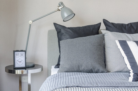room decoration: modern grey lamp with alarm clock on side table in bedroom at home Stock Photo