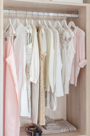 clothes hanging: clothes hanging in wooden wardrobe at home Stock Photo