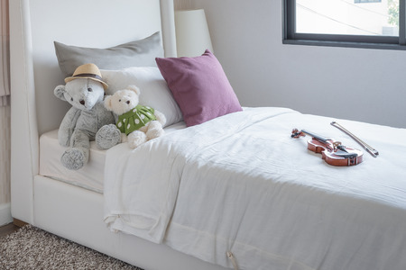 bedroom suite: kids bedroom with dolls and pillow on bed at home