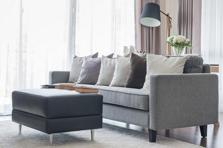 Divano grigio moderno con cuscini e tavolo nero in salotto a casa Archivio Fotografico - 43214946