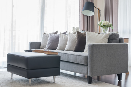 modern grey sofa with pillows and black table in living room at home Standard-Bild
