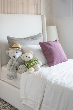 bed room: kids bedroom with dolls and pillow on bed at home