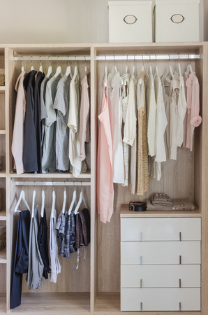 clothes hanging in wooden wardrobe at home Imagens