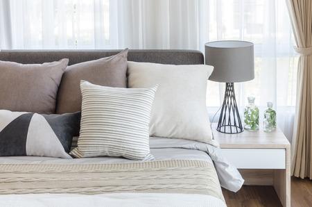 textil: dormitorio de estilo moderno, con almohadas en la cama y la l�mpara gris moderno sobre la mesa lateral en el hogar