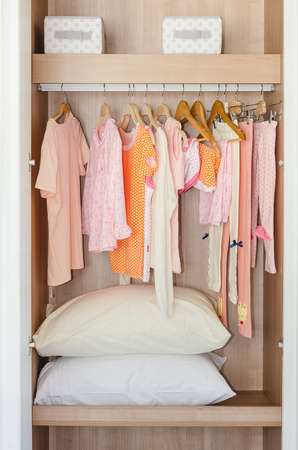 clothes rack: colorful kids clothes hanging on bar in wooden wardrobe with pillows