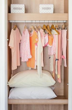 ropa colgada: ropa de colores para niños colgando de la barra de armario de madera con las almohadillas